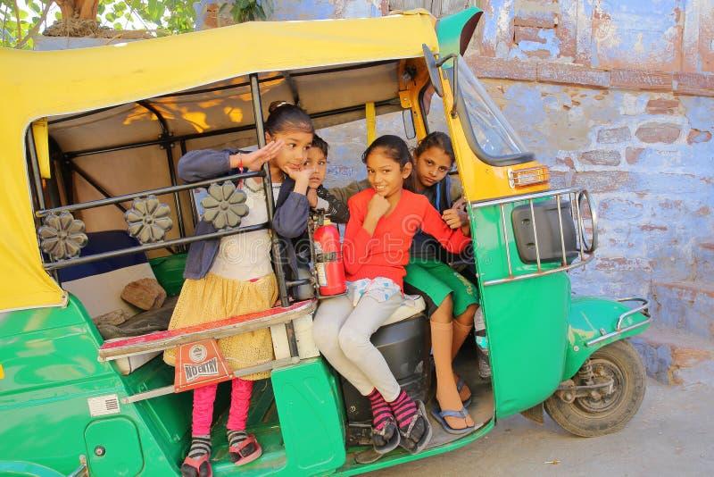 JODHPUR, RAJASTHÁN, LA INDIA - 17 DE DICIEMBRE DE 2017: Retrato de los niños que sonríen y que presentan dentro de un Tuk Tuk fotografía de archivo libre de regalías