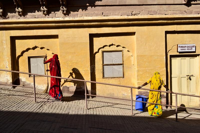 Two women in traditional Indian cloth sweeping the courtyard stock photography