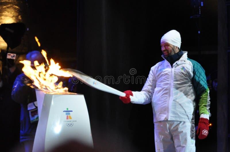 Joe Juneau allume la flamme olympique photographie stock