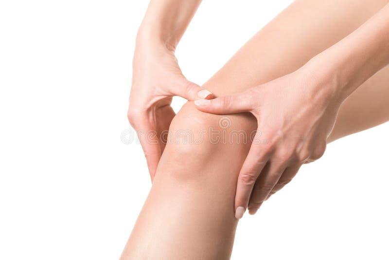 Joelho ferido f?mea A mulher toca em seu ponto dorido no pé pelas mãos Pele bem preparado, fim acima, isolada no branco fotos de stock