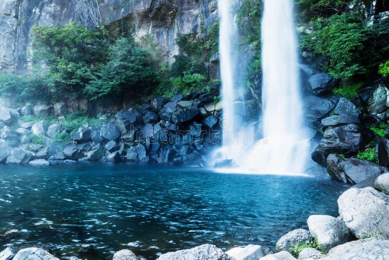 Joengbang瀑布到一个深蓝色水池里在西归浦,济州海岛,韩国 免版税库存照片