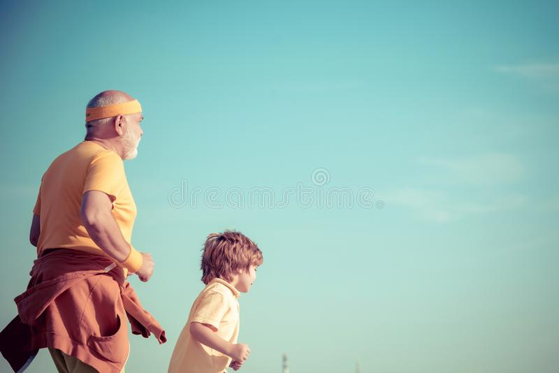 Jog and run marathon for family. Running in park in the morning. Grandpa and grandson is enjoying sporty lifestyle royalty free stock photography