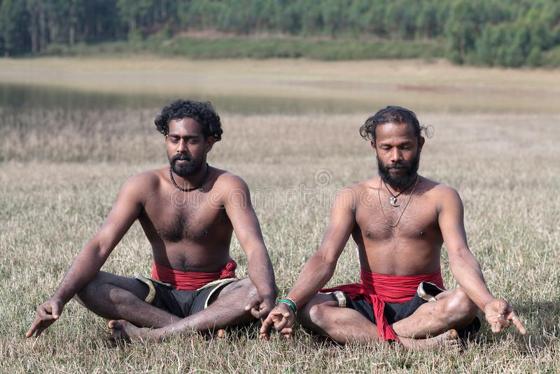 Joga - Indiańscy mężczyźni medytuje w lotosowej joga pozie na zielonej trawie w Kerala, India obraz royalty free