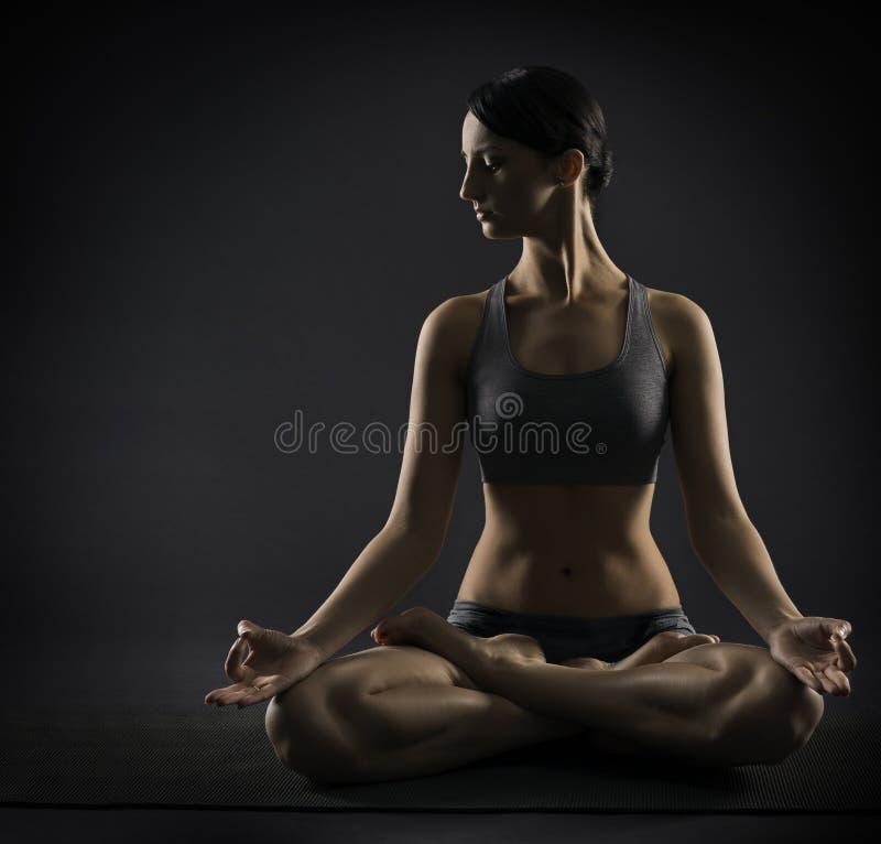 Joga kobieta medytuje obsiadanie w lotos pozie Silhoue zdjęcia stock