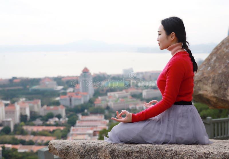Joga kobieta siedzi w medytacji pozie na halnego szczytu skale zdjęcie royalty free