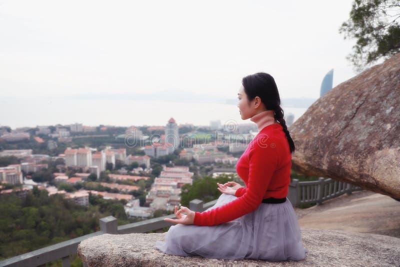 Joga kobieta siedzi w medytacji pozie na halnego szczytu skale obraz royalty free