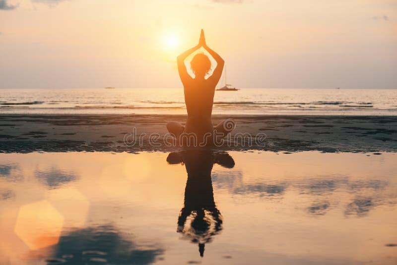 Joga kobiety sylwetka na plaży, jaskrawy zmierzch relaksuje obraz stock