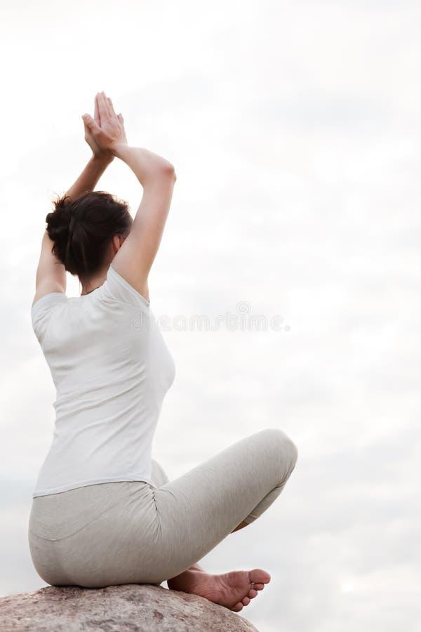 Joga młoda kobieta robi łatwym ćwiczeniom siedzi w lotos pozie na kamieniu obrazy stock
