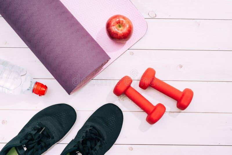 Joga matuje, sportów buty, dumbbells i butelka woda na błękitnym bac, zdjęcia royalty free