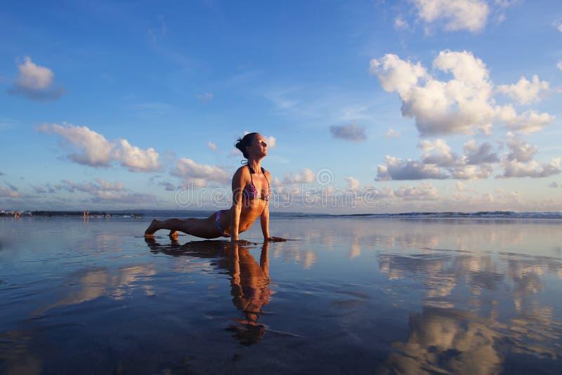 Joga na plaży przy zmierzchem obrazy royalty free
