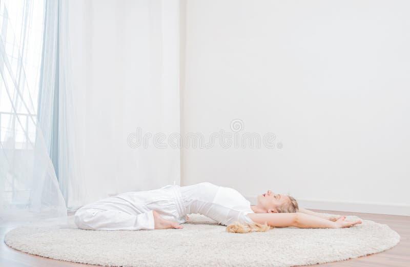 joga Piękna kobieta ćwiczy joga w domu, dziewczyna robi Supta Virasanaexercise pozie zdjęcie stock
