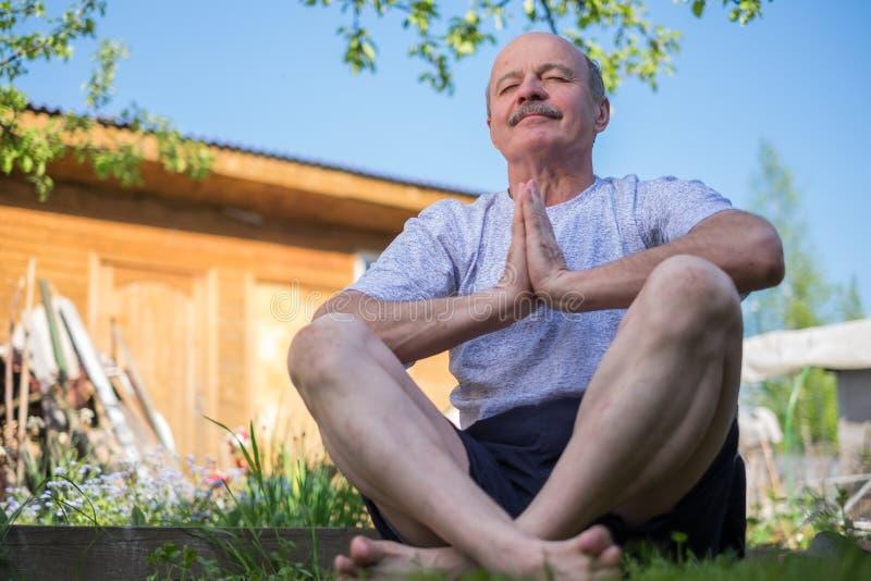 Joga przy parkiem Starszy mężczyzna z wąsy z namaste obsiadaniem Pojęcie spokój i medytacja obraz royalty free