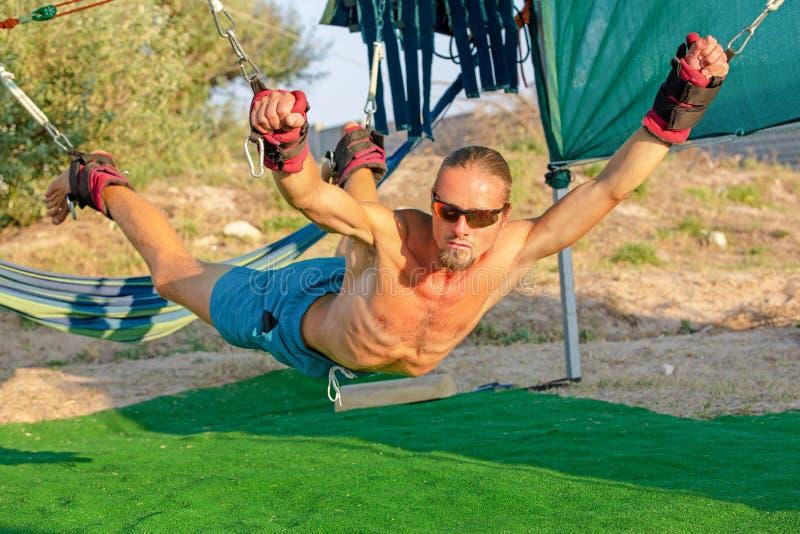 Joga traktowanie dla sedna, joga huśta się, szczupły młody człowiek troczący cztery deski nad ziemia, mężczyzna rozwija wytrzymał obrazy stock