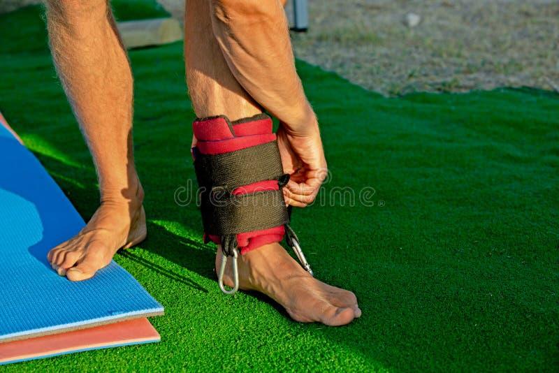 Joga traktowanie dla sedna, szczupły młody człowiek używa joga huśtawki rozwija wytrzymałość i rozciąga sedna zdjęcie royalty free
