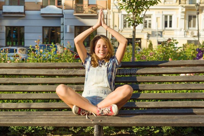 Joga w mieście, nastoletnia dziewczyna siedzi w lotosowej pozie na ławce w miasto parku Relaksuje, odpoczywa, medytacja zdjęcia stock
