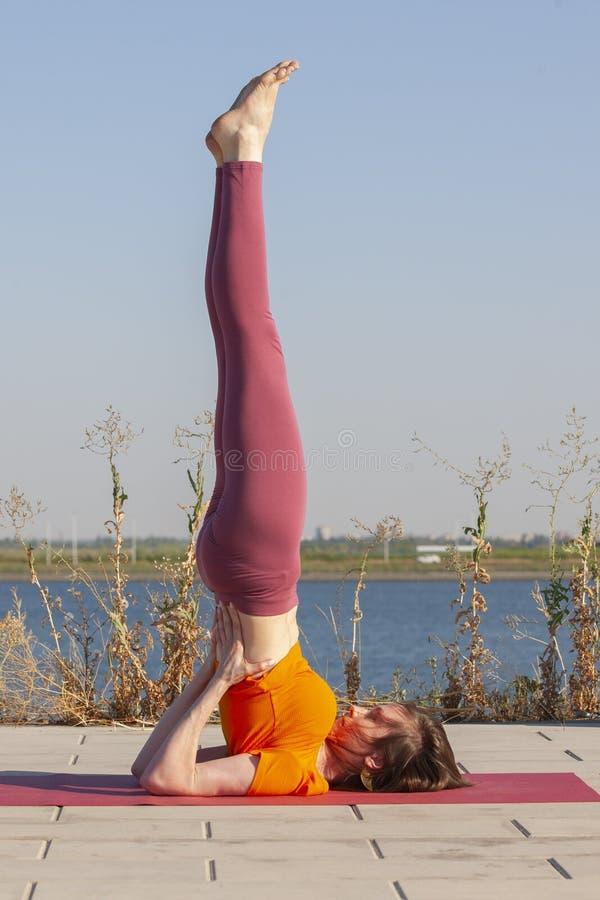 joga zewn?trznego Szcz??liwa kobieta robi joga ?wiczeniom, medytuje w parku Joga medytacja w naturze Poj?cie zdrowy styl ?ycia i zdjęcie stock