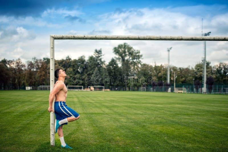 Jogador da aptidão que dá certo no campo de futebol Formação apta da cruz fora em um dia de verão imagens de stock royalty free