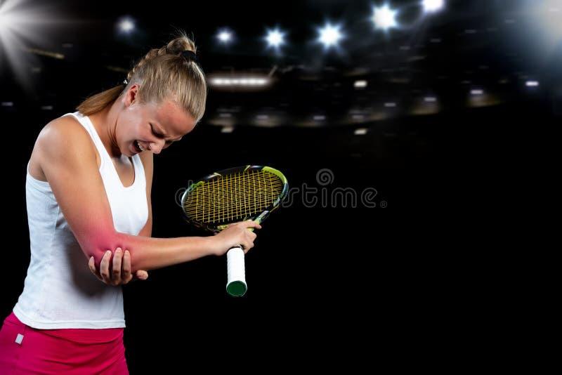 Jogador da mulher do tênis com ferimento que guarda a raquete em um campo de tênis imagens de stock
