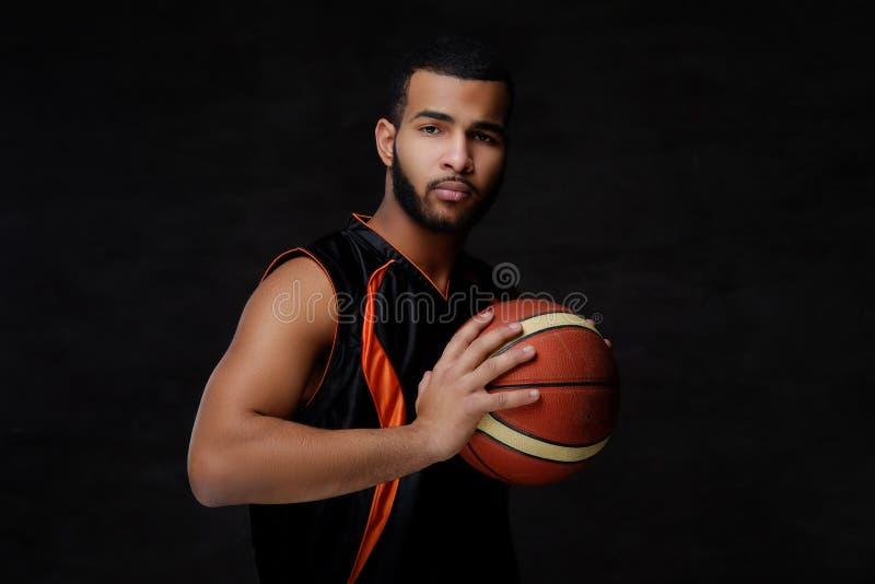 Jogador de basquetebol afro-americano novo no sportswear isolado sobre o fundo escuro imagens de stock royalty free