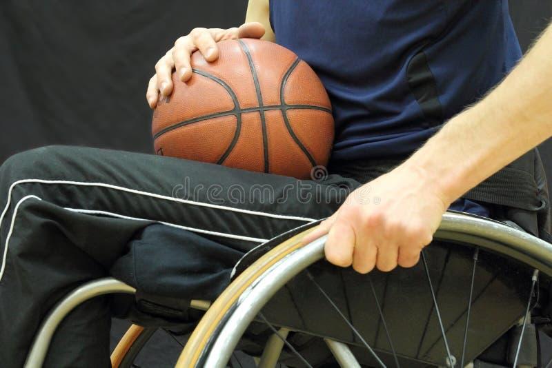 Jogador de basquetebol da cadeira de rodas com a bola em seu regaço fotos de stock