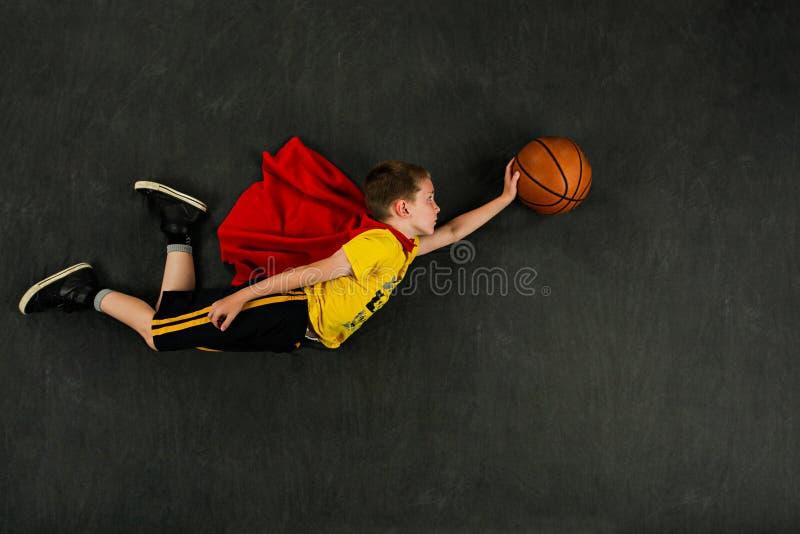 Jogador de basquetebol do super-herói do menino imagem de stock