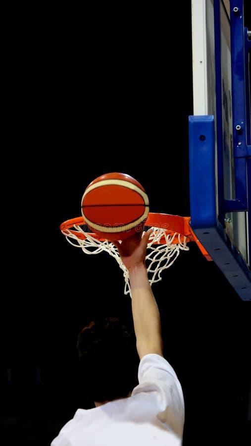 Jogador de basquetebol durante o esmagamento da cesta com os bas imagem de stock