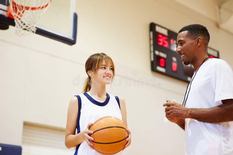 Jogador de basquetebol fêmea da High School que fala com treinador foto de stock
