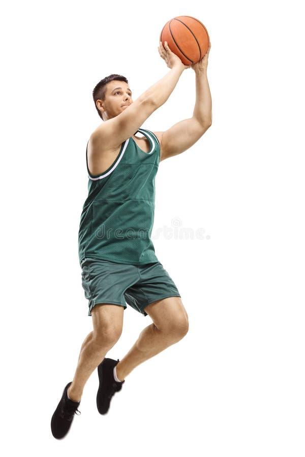 Jogador de basquetebol masculino que dispara em uma bola fotos de stock