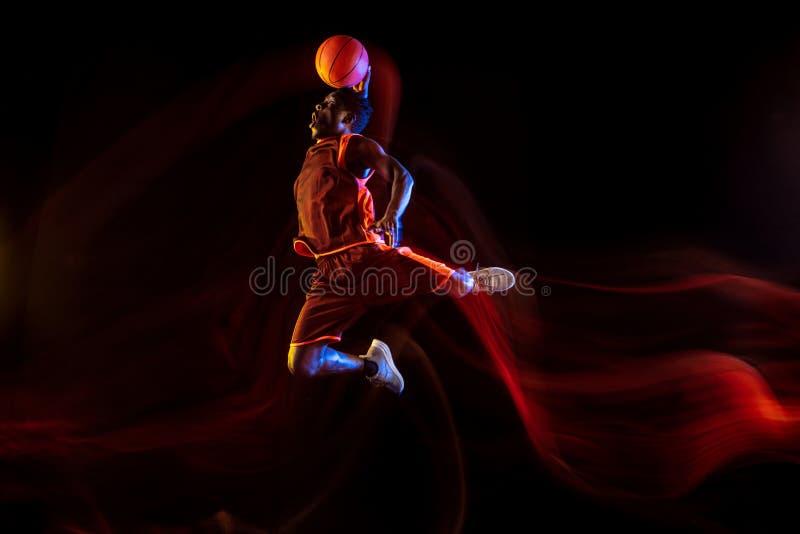 Jogador de basquetebol novo contra o fundo escuro fotos de stock royalty free