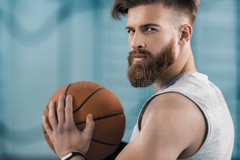 Jogador de basquetebol novo que guarda a bola e que olha a câmera fotos de stock