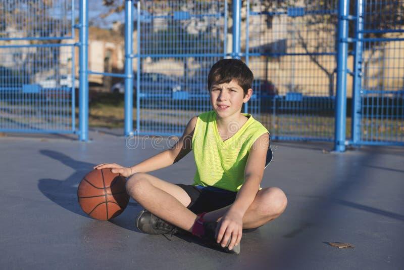Jogador de basquetebol novo que senta-se na corte imagens de stock royalty free