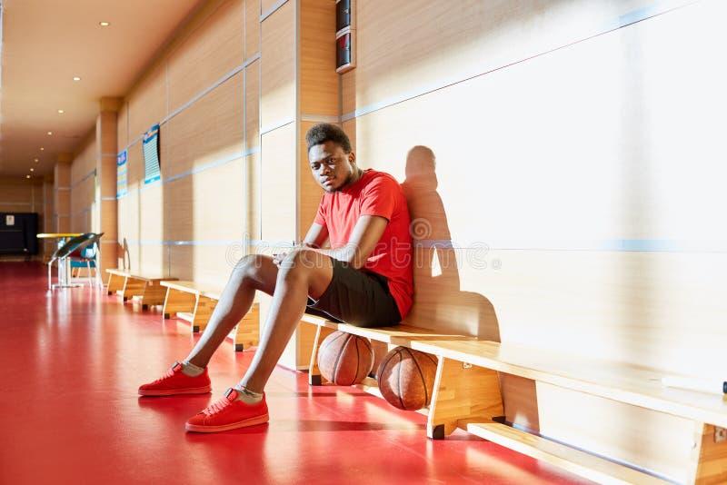 Jogador de basquetebol preto que descansa no banco fotografia de stock
