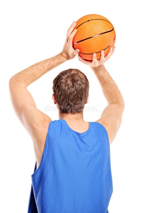 Jogador de basquetebol que aponta disparar em uma esfera fotos de stock