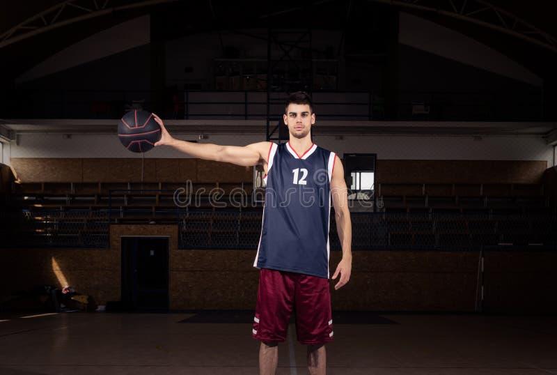 Jogador de basquetebol que guarda a bola em uma mão fotografia de stock