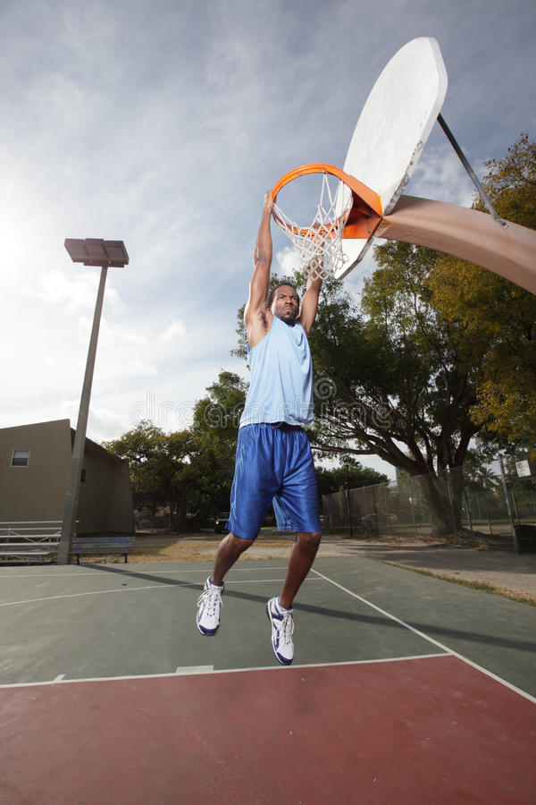Jogador de basquetebol que pendura da aro imagem de stock