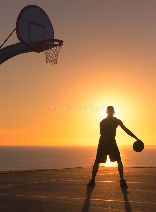 Jogador de basquetebol que pinga uma bola no por do sol Silhueta fotos de stock royalty free