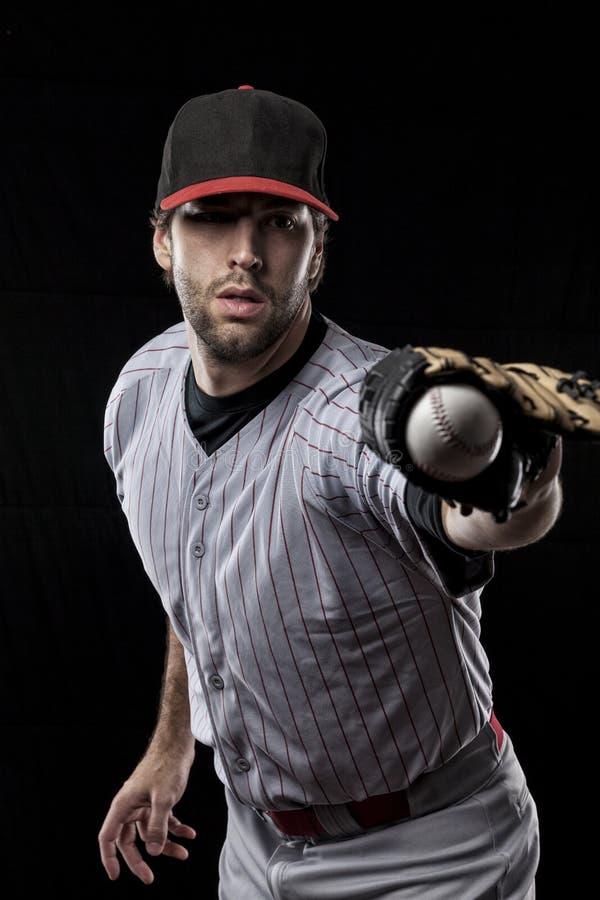 Jogador de beisebol em um uniforme vermelho. fotografia de stock royalty free