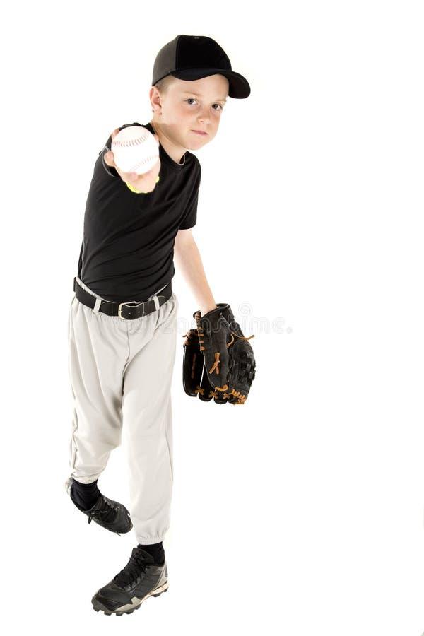 Jogador de beisebol novo que joga a bola na câmera fotografia de stock