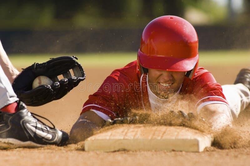 Jogador de beisebol que desliza na base fotografia de stock royalty free
