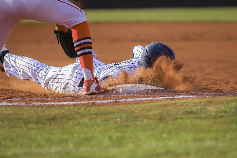 Jogador de beisebol que desliza a primeira base fotografia de stock