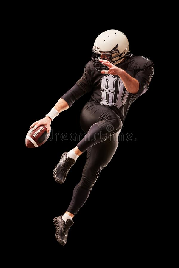 Jogador de futebol americano em um salto com uma bola em um fundo preto imagens de stock royalty free
