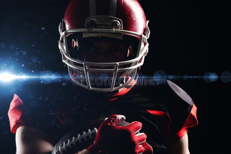 Jogador de futebol americano no capacete que guarda a bola de rugby foto de stock