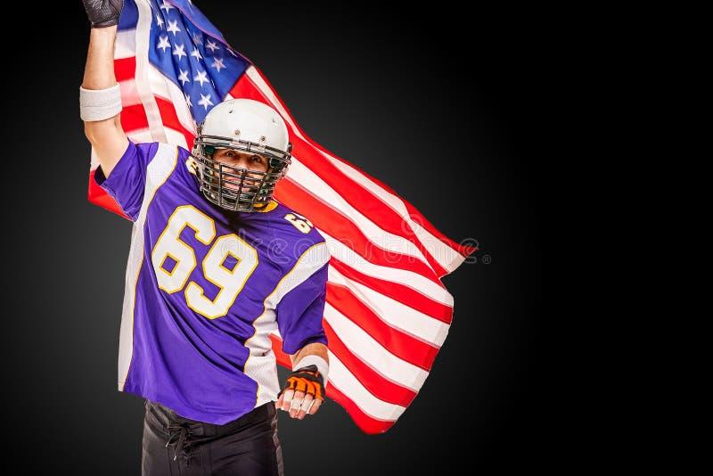 Jogador de futebol americano patriótico que levanta na câmera no fundo preto com bandeira dos EUA O conceito do patriotismo, cham imagens de stock