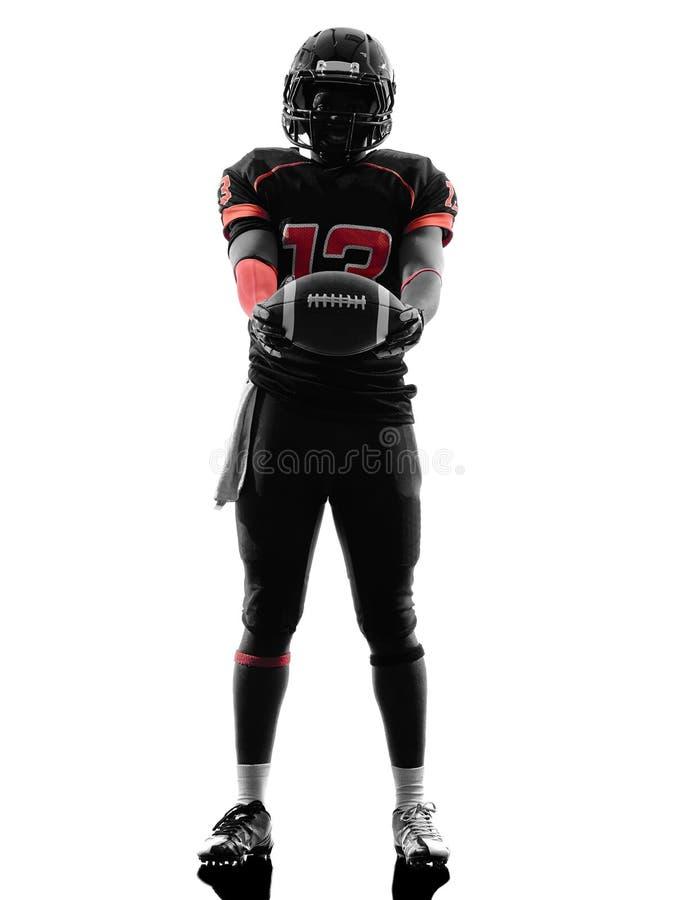Jogador de futebol americano que está guardando a silhueta da bola foto de stock