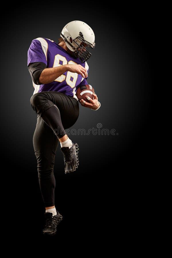 Jogador de futebol americano que guarda uma bola ao saltar longe de uma greve fundo preto, espa?o da c?pia Violeta com imagens de stock