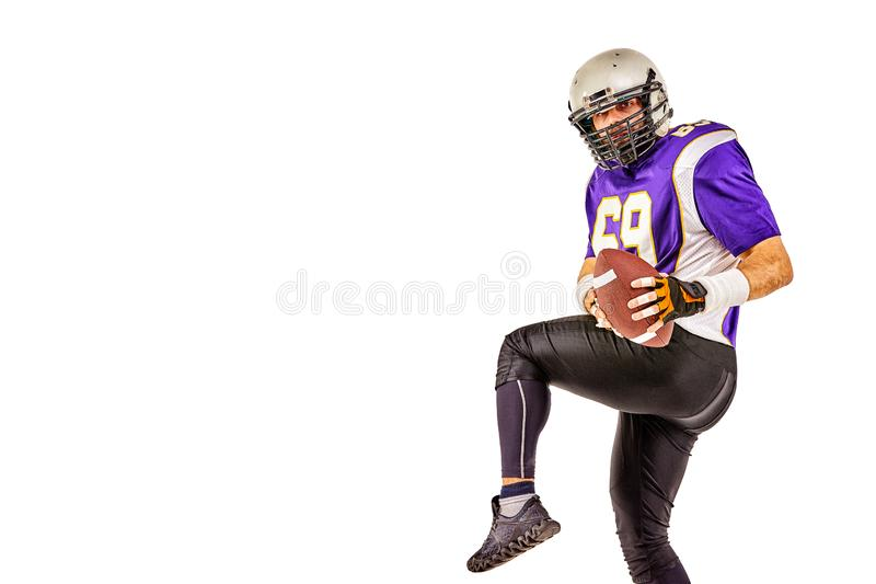 Jogador de futebol americano que levanta com a bola no fundo preto Formato quadrado Futebol americano do conceito, retrato foto de stock