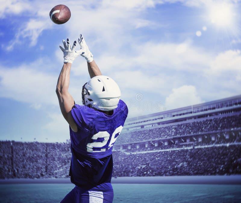 Jogador de futebol americano que trava uma passagem de aterrissagem imagem de stock royalty free