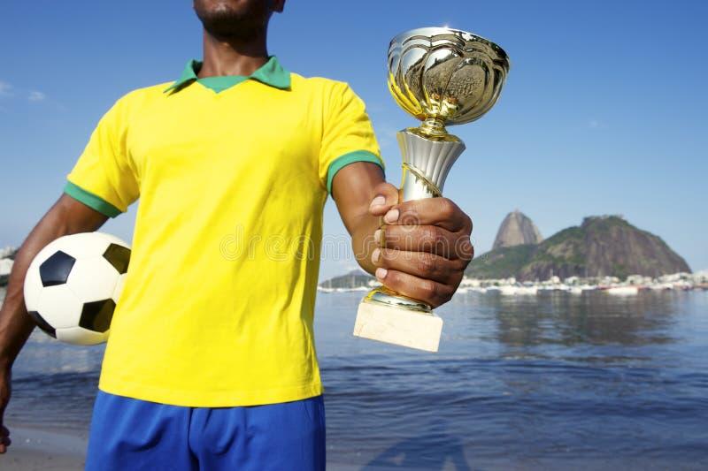 Jogador de futebol brasileiro do campeão que guarda o troféu e o futebol fotos de stock