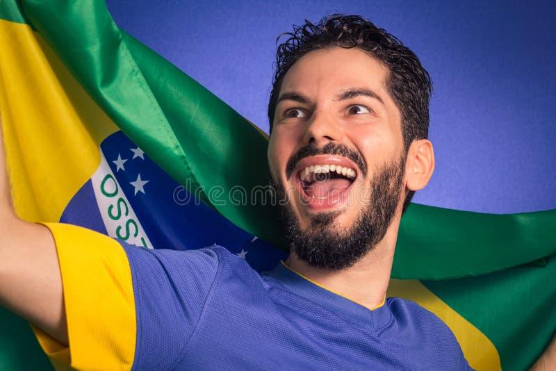 Jogador de futebol brasileiro do futebol que guarda a bandeira de Brasil fotos de stock