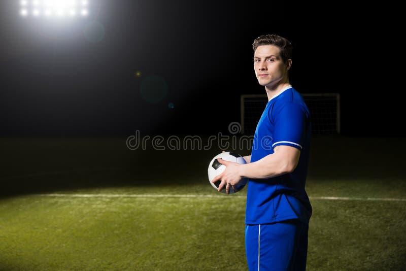 Jogador de futebol com a bola no campo de futebol imagem de stock